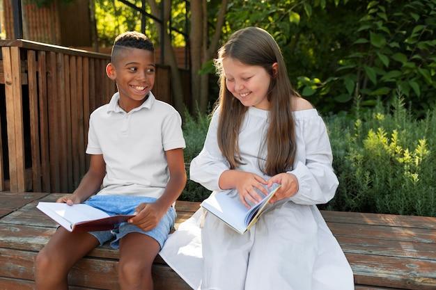 야외에서 책을 읽는 미디엄 샷 아이들