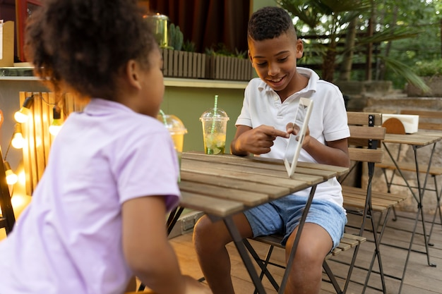 태블릿이 있는 테이블에 앉아 있는 중간 샷 아이들