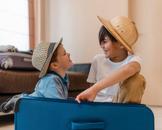 Bambini di tiro medio seduti nel bagaglio