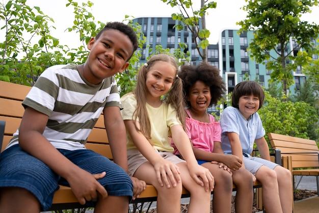 ベンチに座っているミディアムショットの子供たち