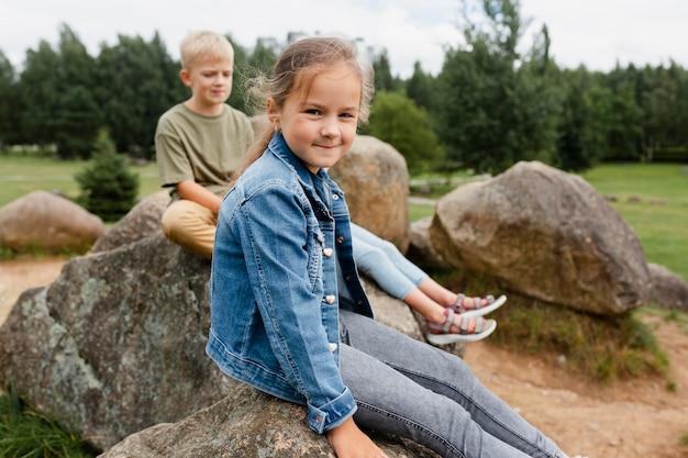 岩の上に座っているミディアムショットの子供たち
