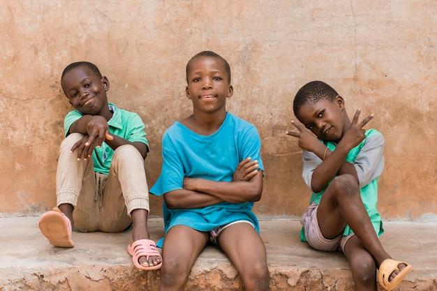 屋外に座っているミディアムショットの子供たち