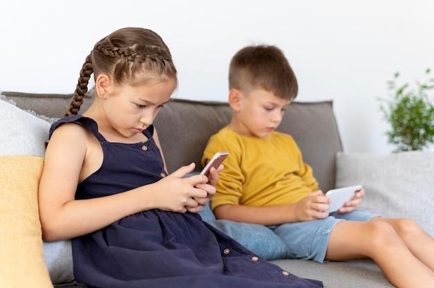 Дети среднего кадра с устройствами в помещении