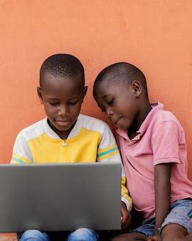 ノートパソコンを持ったミディアムショットの子供