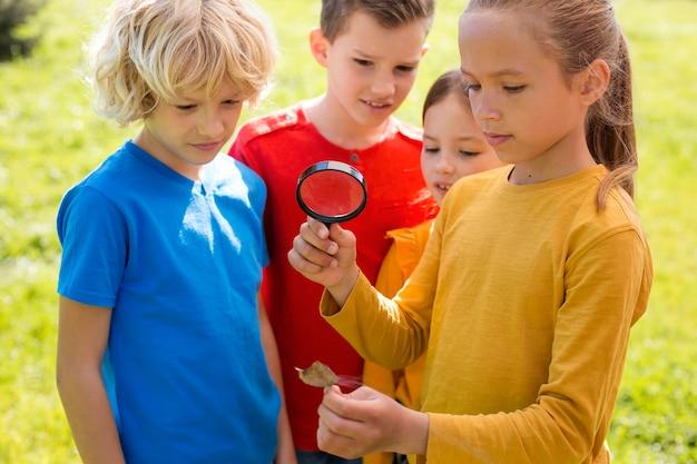 Дети среднего кадра с увеличительным стеклом