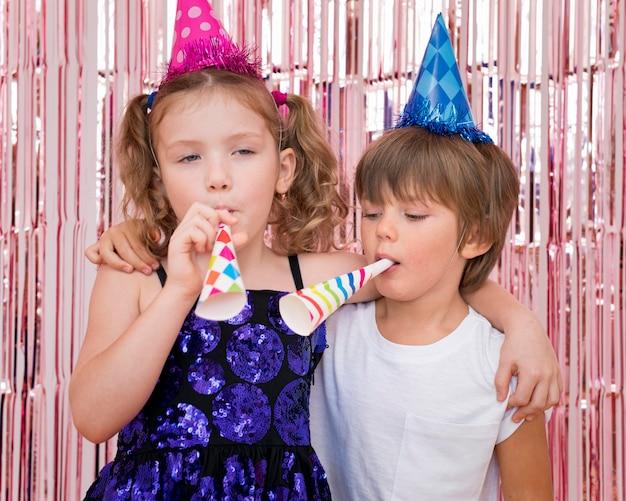 パーティーホイッスルのミディアムショットの子供たち