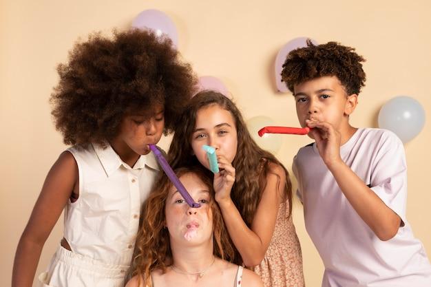 パーティーの笛を吹くミディアムショットの子供たち