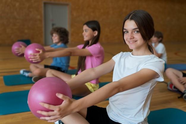 ピンクのボールを持つミディアムショットの子供たち