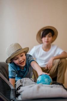Bambini a tiro medio con globo del mondo