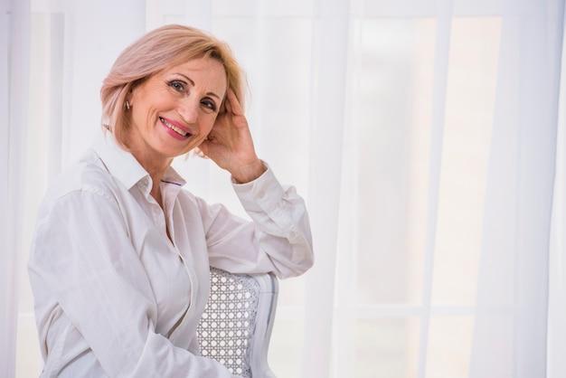 Дама среднего роста с короткими волосами смотрит в камеру с копией пространства