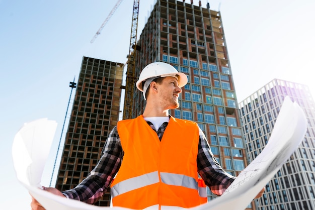 Medium shot low angle view of construction engineer holding plans