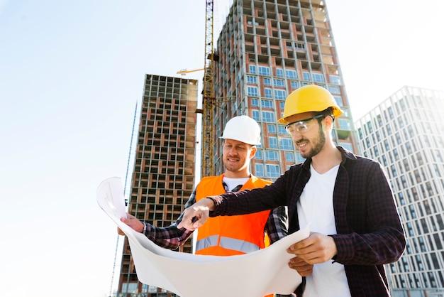 Средний снимок с низким углом зрения инженера и архитектора, осуществляющего надзор за строительством