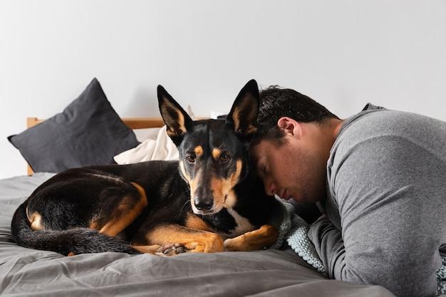 ミディアムショットの男と愛らしい犬を室内で