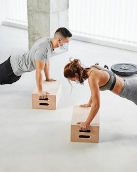 Мужчина и женщина среднего роста делают отжимания