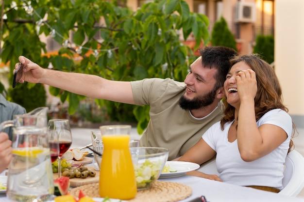 Средний снимок мужчины и женщины, делающих селфи