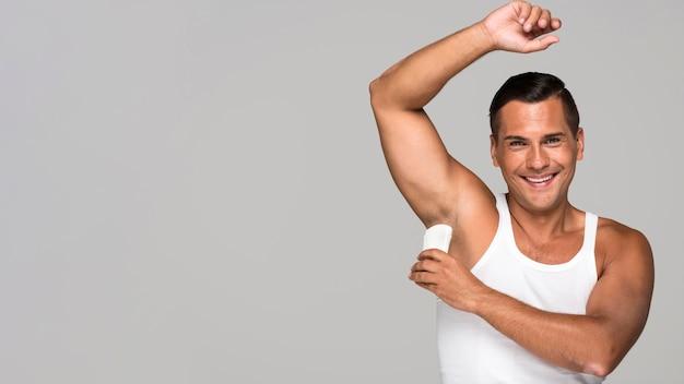 Uomo del colpo medio che applica deodorante