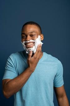 Uomo di tiro medio che applica crema da barba