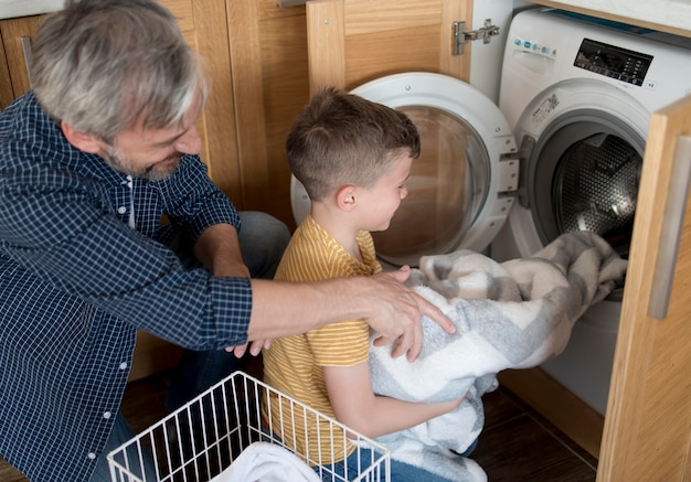 Uomo e ragazzo del colpo medio che fanno il bucato
