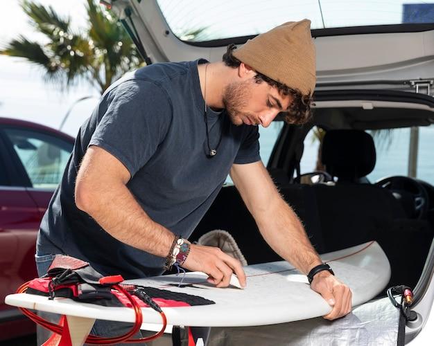 ミディアムショットの男がサーフボードを掃除する