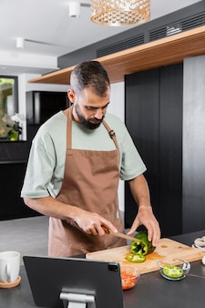 Medium shot man cutting vegetable
