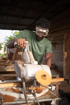 ミディアムショットの男が木を切る