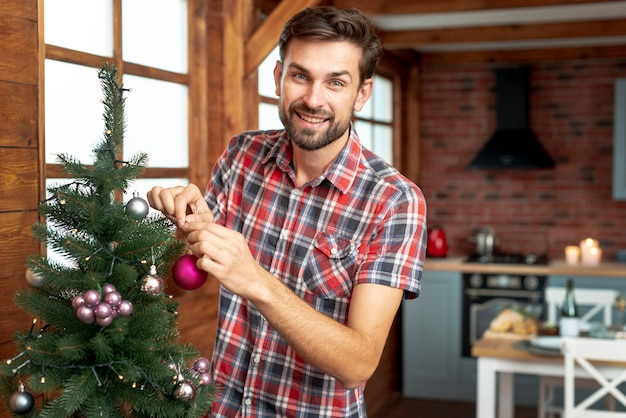 Medium shot man decorating the christmas tree with pink balls