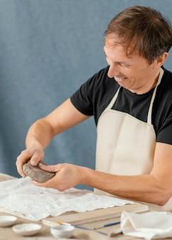 自宅で陶器をやっているミディアムショットの男