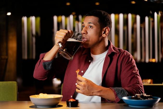 술집에서 맥주를 마시는 중간 샷된 남자