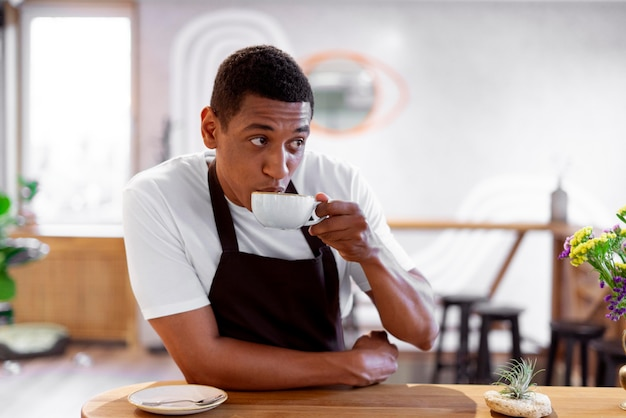 Uomo di tiro medio che beve caffè