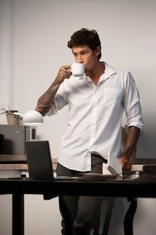 コーヒーを飲むミディアムショットの男