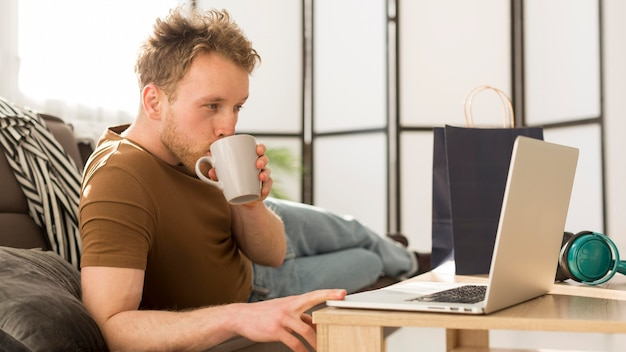 Medium shot man drinking from mug
