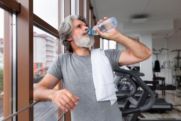 ミディアムショットの男がジムで水を飲む