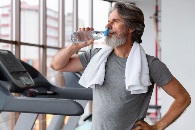 Medium shot man drinking water at gym