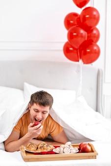 Medium shot man eating in bedroom