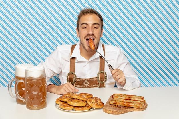 Medium shot of man eating german sausages