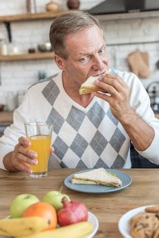Medium shot man eating a sandwich
