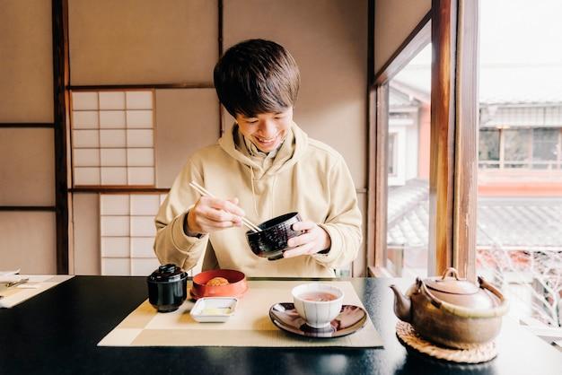 箸で食べるミディアムショットの男