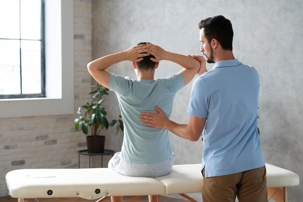 물리 치료에서 환자를 돕는 중간 샷 남자