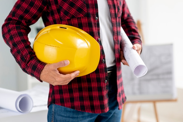 Medium shot man holding architectural plans and safety helmet