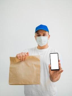 Medium shot man holding bag and phone