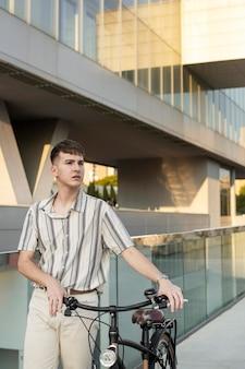 Uomo di tiro medio che tiene il manubrio della bici