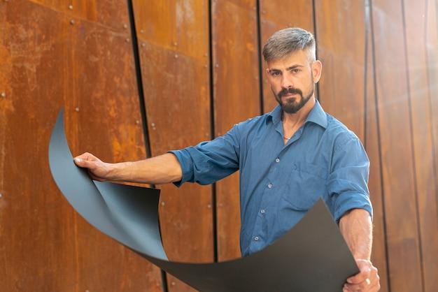 Medium shot of man holding blueprint