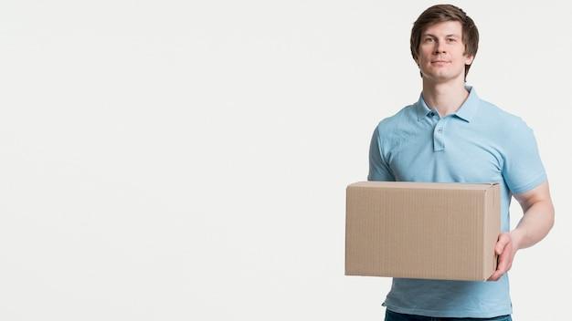 Средний выстрел мужчина держит коробку