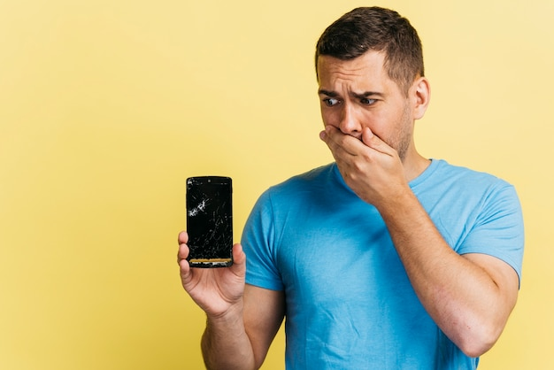 Medium shot man holding a broken phone