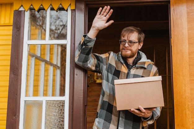Средний выстрел мужчина держит картонную коробку