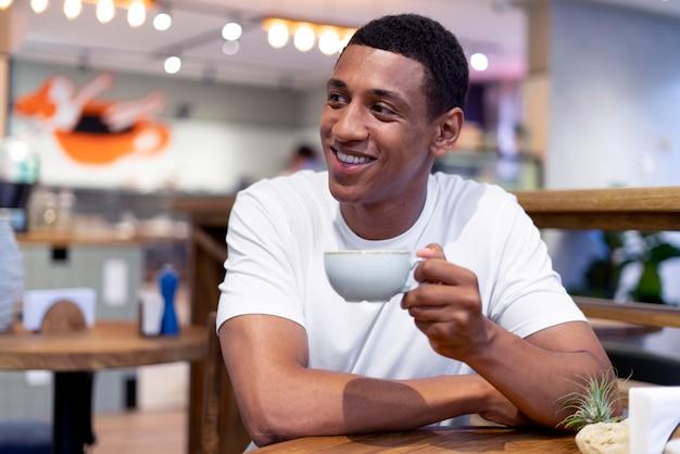 Medium shot man holding coffee cup