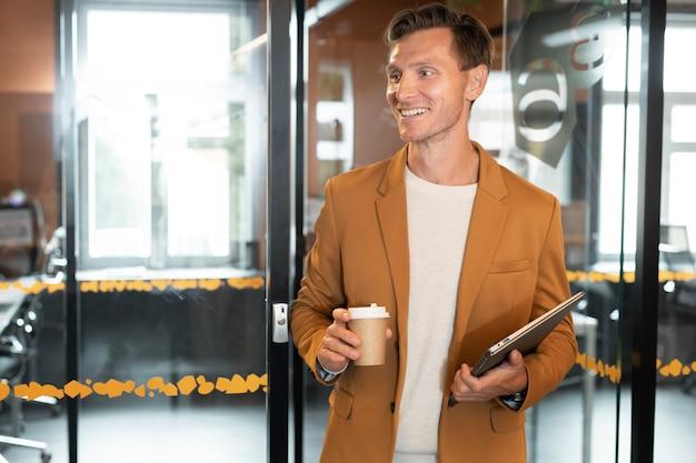 コーヒーカップを持っているミディアムショットの男
