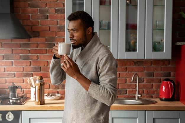 실내에서 컵을 들고 있는 중형 남자