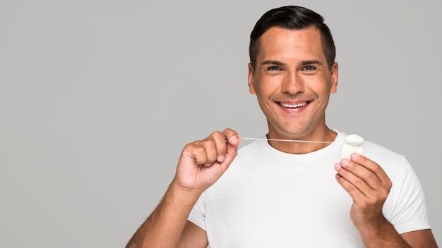 Medium shot man holding dental floss