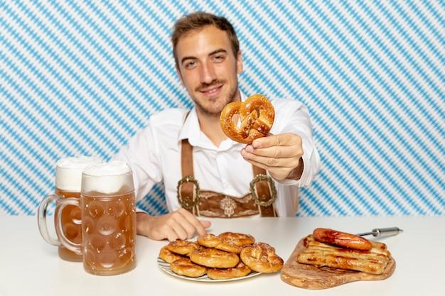 Medium shot of man holding german pretzel